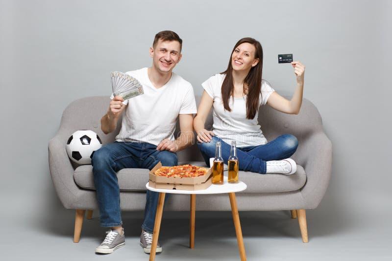 微笑的夫妇妇女人足球迷在美元钞票支持拿着信用万一银行卡,金钱爱好者的喜爱的队  库存图片