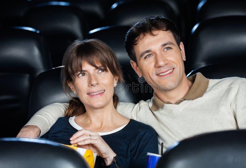 微笑的夫妇观看的电影在剧院 免版税库存照片