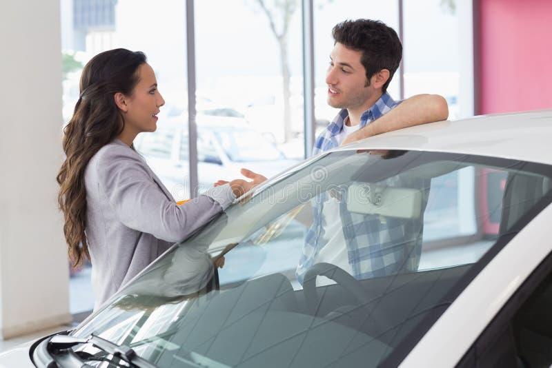 微笑的夫妇谈话在汽车旁边 免版税图库摄影