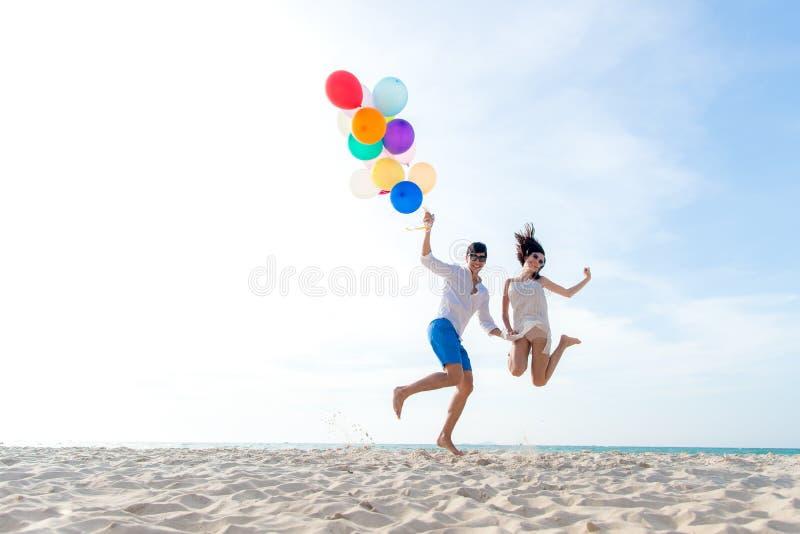 微笑的夫妇递结合在一起使气球和跳跃在海滩 浪漫的恋人和在暑假放松蜜月 Summ 免版税库存照片