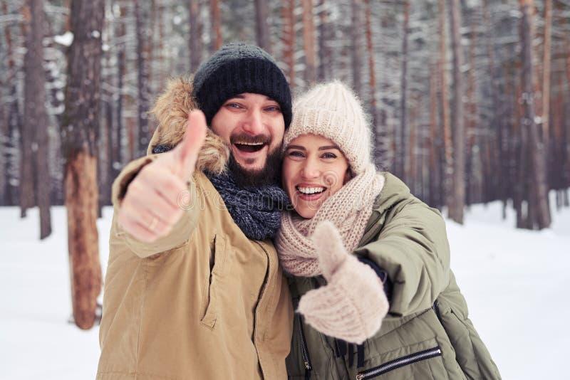微笑的夫妇降雪的赞许打手势和拥抱在冷的w 免版税库存图片