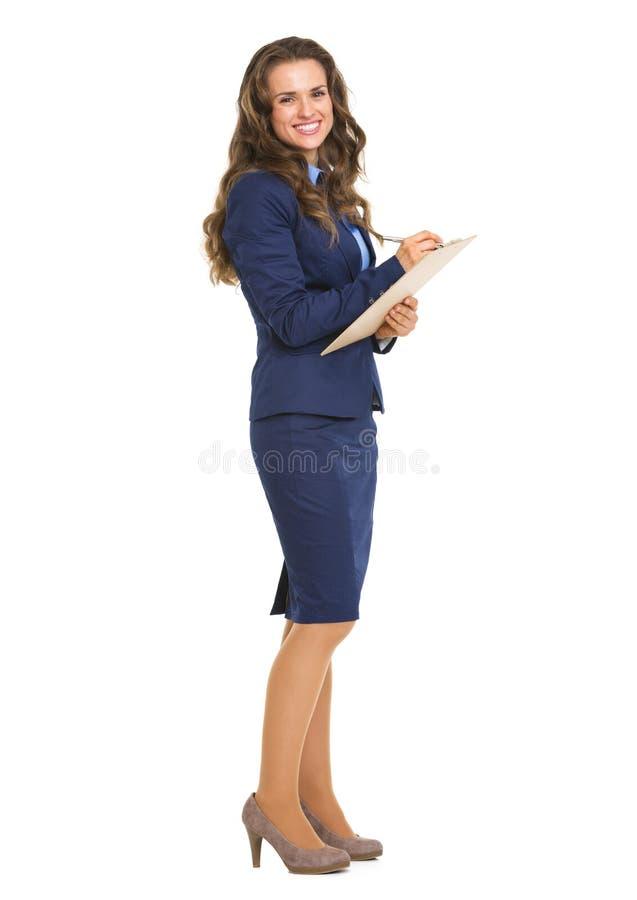 微笑的女商人文字画象在剪贴板的 免版税库存照片