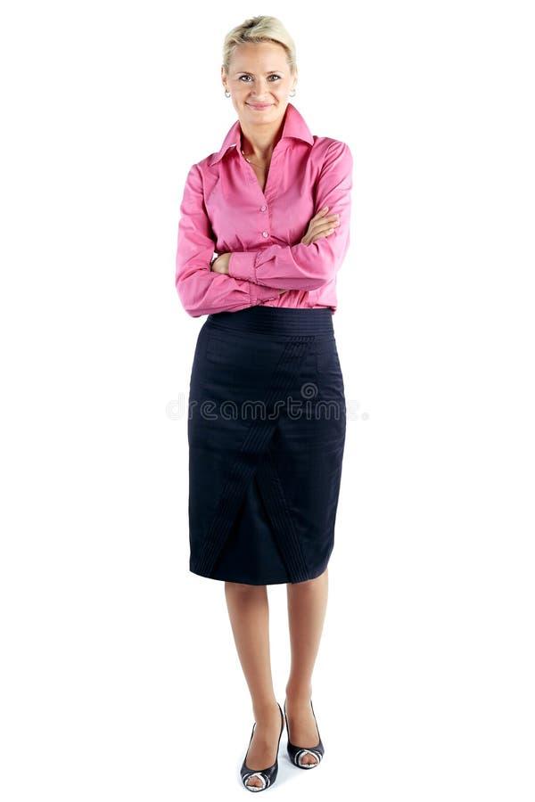 微笑的女商人用反对白色backgroun的被折叠的手 免版税库存照片