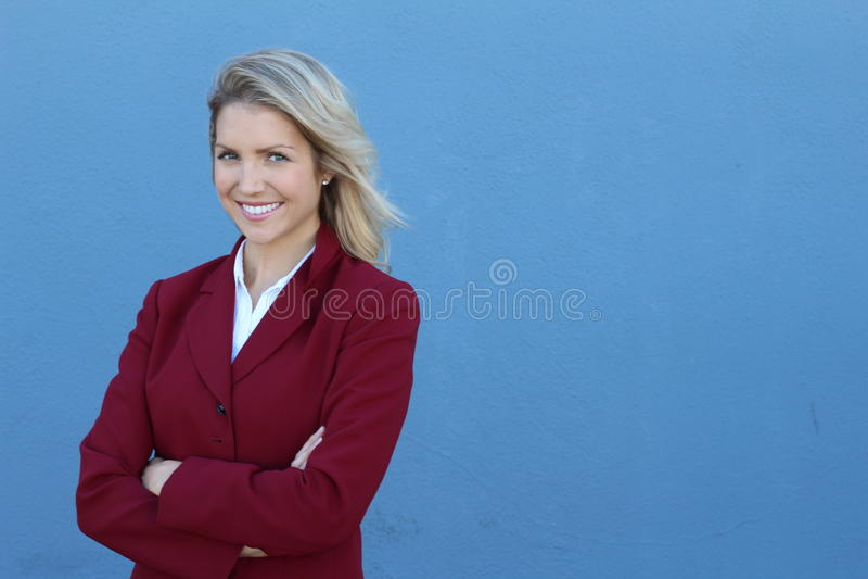 微笑的女商人用反对蓝色背景的被折叠的手 暴牙的微笑,横渡的胳膊 库存照片