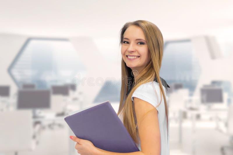 微笑的女商人画象有纸文件夹的 在办公室 免版税库存图片