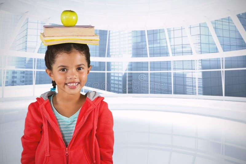 微笑的女孩分类帐余额簿和苹果的综合图象在头 库存图片