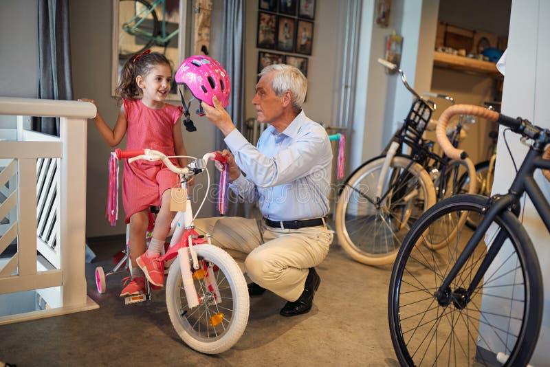 微笑的女孩和她的祖父购买自行车和盔甲在自行车商店 免版税库存照片