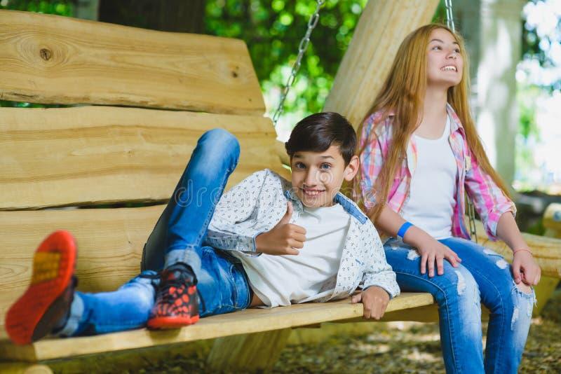微笑的女孩和男孩获得乐趣在操场 使用户外在夏天的孩子 摇摆的少年 库存图片
