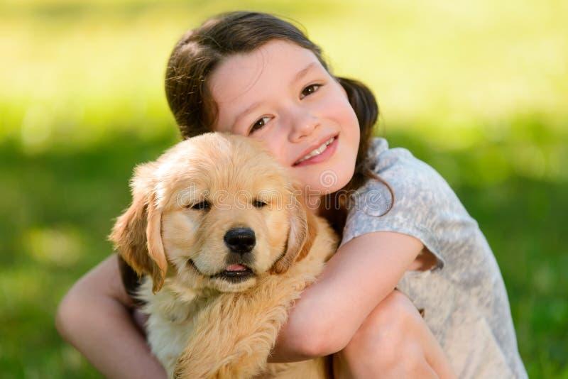 微笑的女孩和金毛猎犬 库存照片