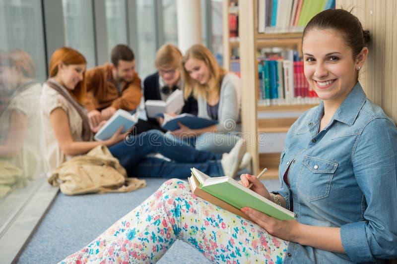 微笑的女孩在大学图书馆里 库存图片