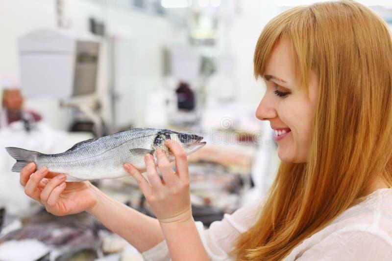 微笑的女孩在存储拿着鱼 库存图片