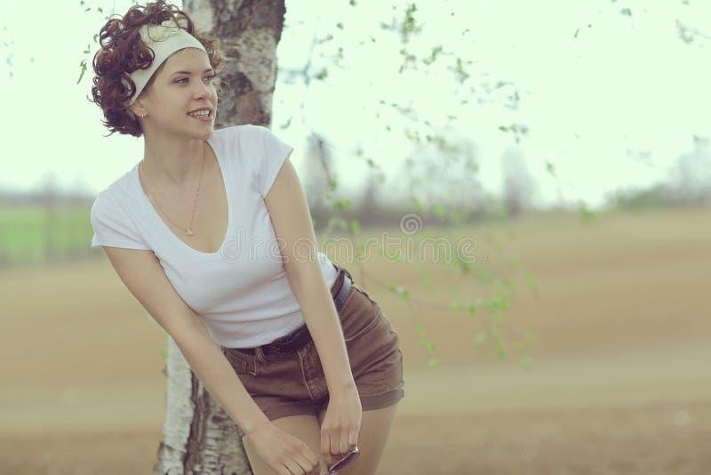 微笑的女孩在春天森林里 免版税库存图片