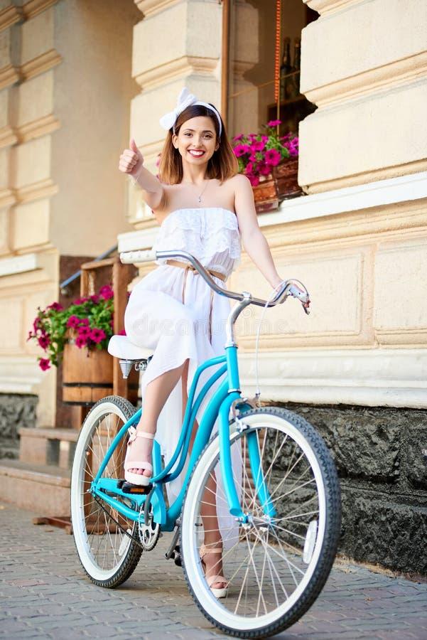微笑的女孩坐减速火箭的自行车展示分类,老城市 免版税库存照片