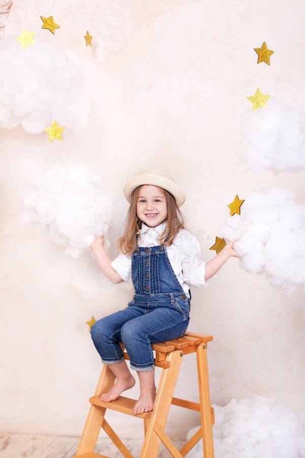 微笑的女孩坐在天空的台阶与云彩和与星 一点天文学家小旅客 女孩飞行  免版税库存照片