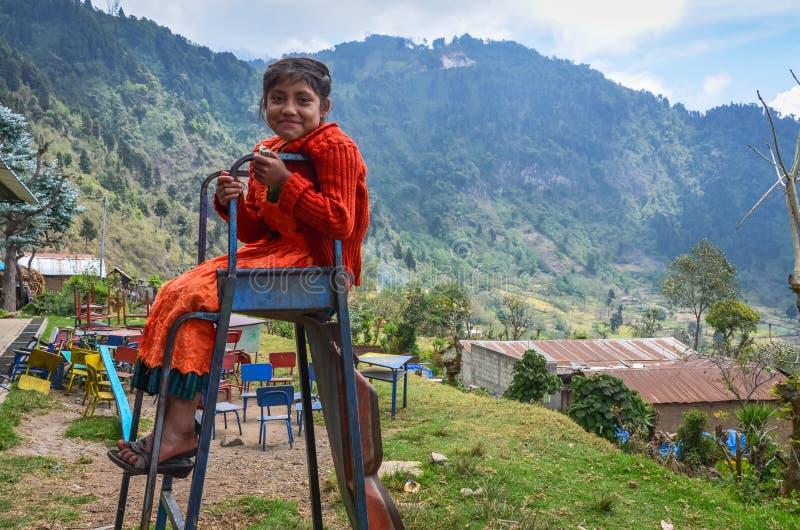 微笑的女孩坐残破的幻灯片在危地马拉 图库摄影