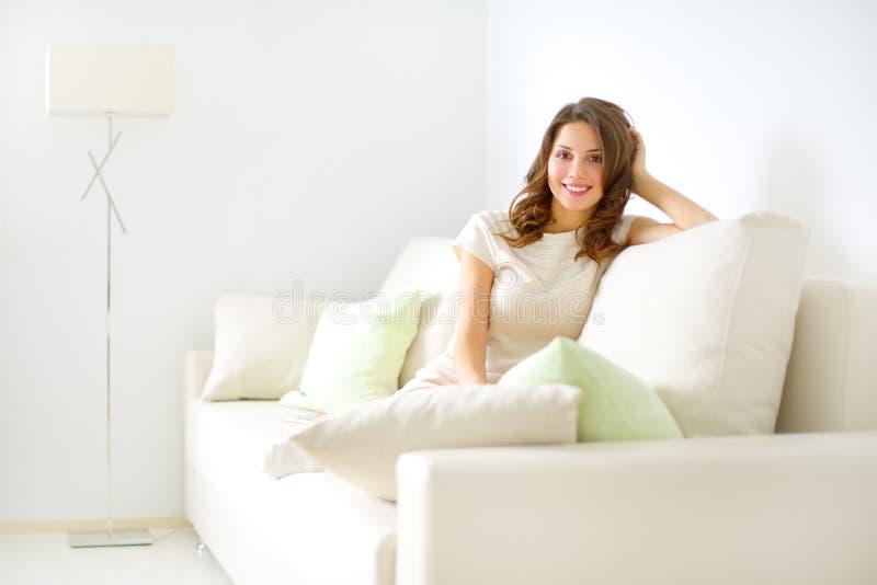 微笑的女孩坐沙发 库存照片