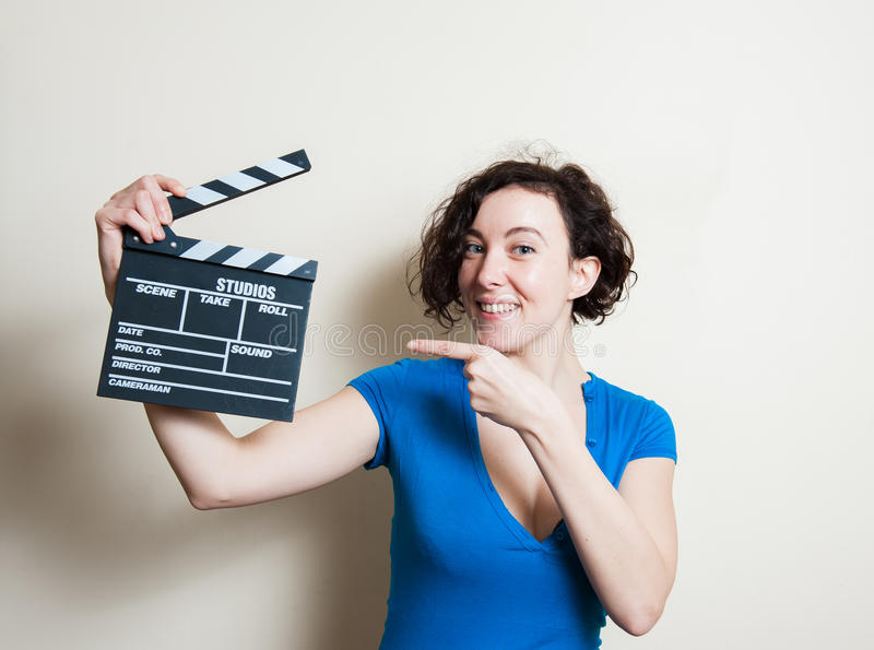 微笑的女孩指出在白色背景的电影拍板 免版税库存图片