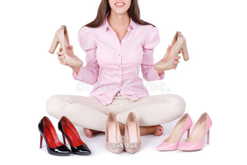 微笑的女孩提出在白色背景隔绝的四个现代对高跟鞋 库存照片