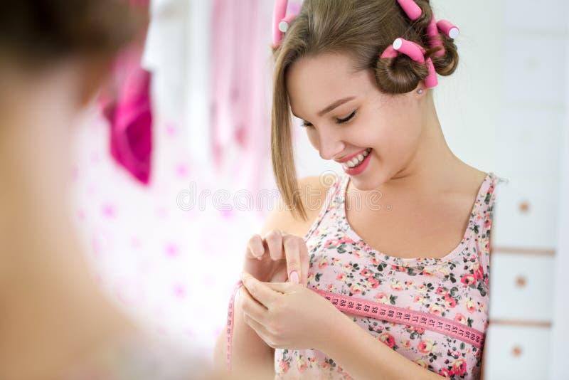 微笑的女孩测量的乳房 免版税库存图片