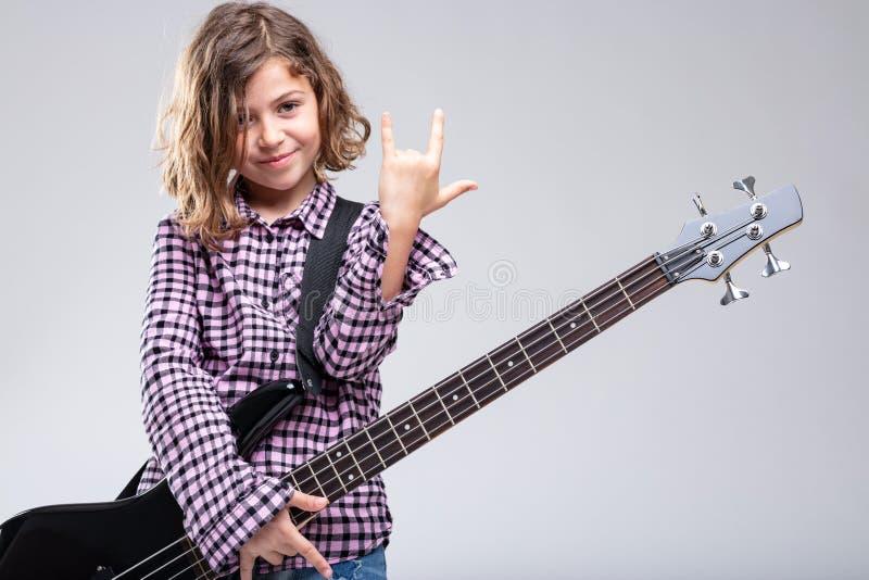 微笑的女孩演奏吉他给垫铁签字 免版税库存图片