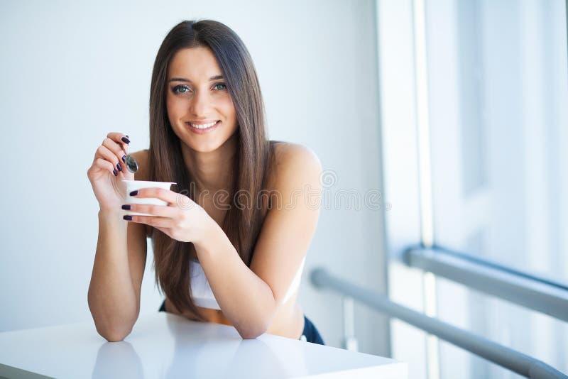 微笑的女孩用酸奶 品尝新鲜的有机酸奶的年轻微笑的妇女坐在白色明亮的室,佩带  免版税库存图片