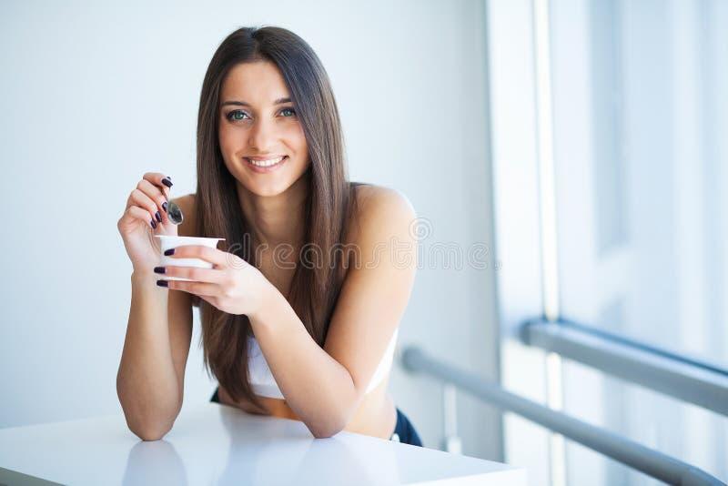 微笑的女孩用酸奶 品尝新鲜的有机酸奶的年轻微笑的妇女坐在白色明亮的室,佩带  免版税库存照片