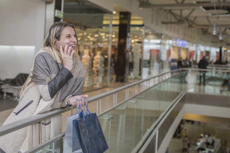 微笑的女孩谈话在她的在商城的手机,当时 库存照片