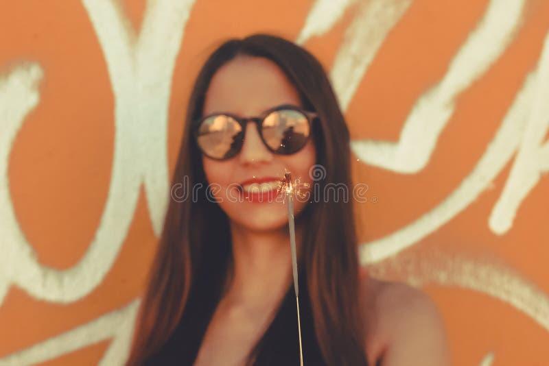 微笑的女孩,当使用闪烁发光物时 免版税库存照片