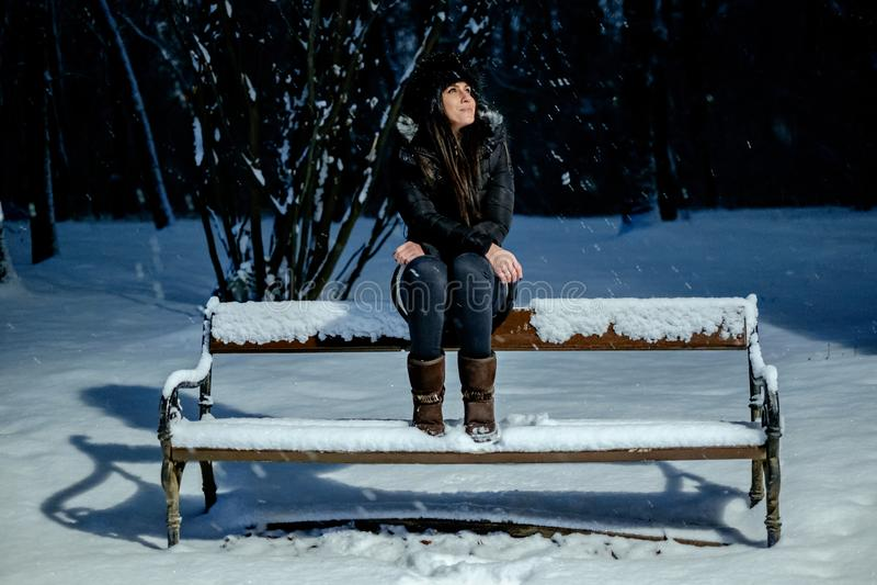 微笑的女孩,当看降雪在公园时 库存照片