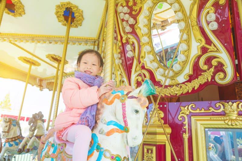 微笑的女孩,当骑在旋转木马时的一匹马 库存照片