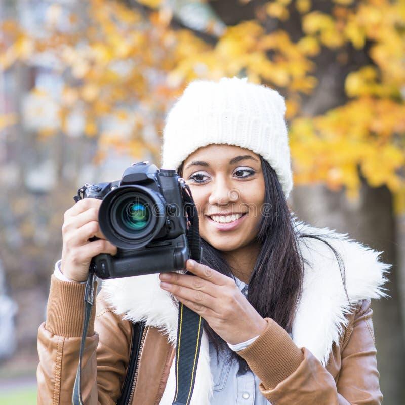 微笑的女孩画象有帽子和照相机的,秋天。 库存照片
