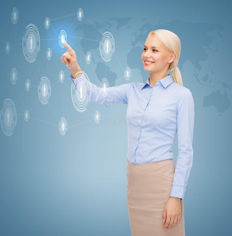微笑的女实业家与虚屏一起使用 免版税库存图片