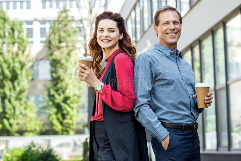 微笑的女实业家和成熟商人用咖啡 免版税库存照片