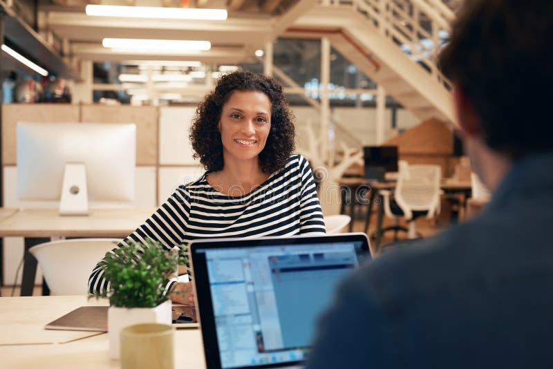 微笑的女实业家在与一个同事的工作在办公室 库存照片