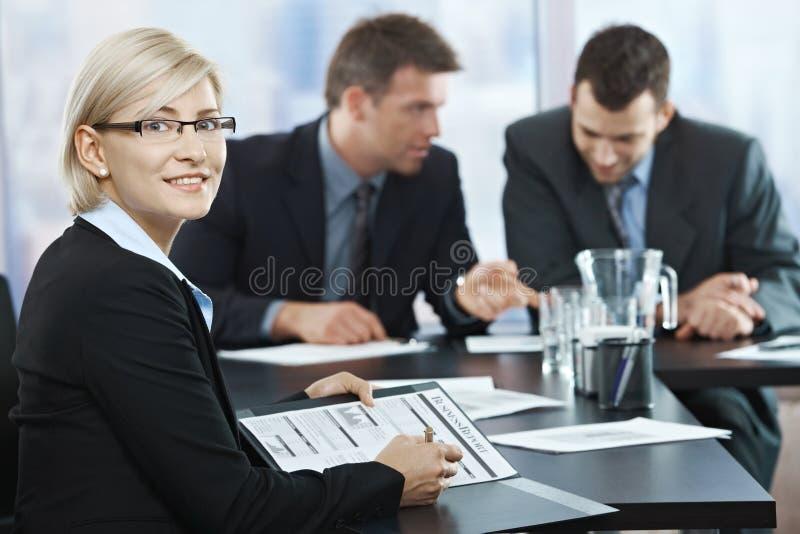 微笑的女实业家在会议上 库存图片