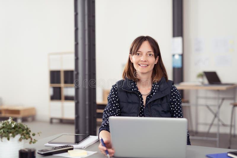 微笑的女实业家在她的与膝上型计算机的表上 库存照片