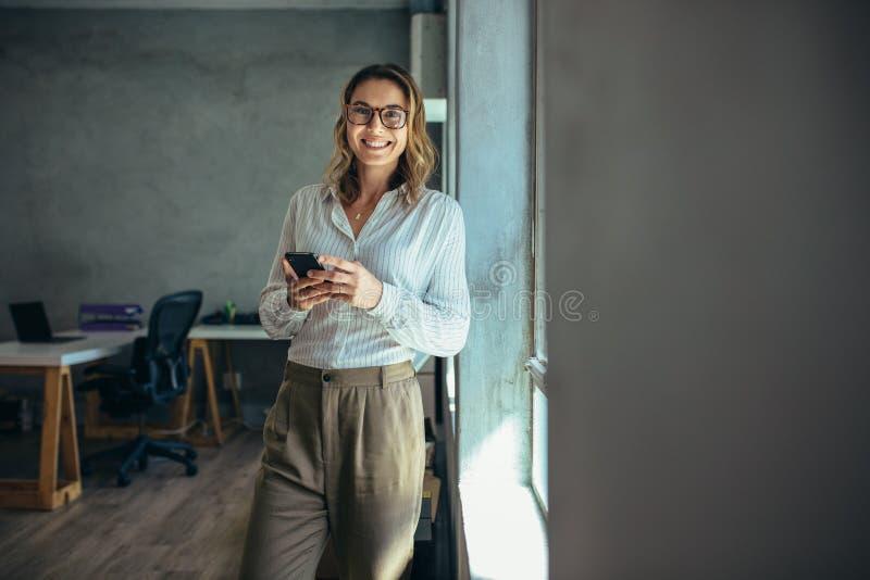 微笑的女实业家在工作在办公室 免版税库存照片