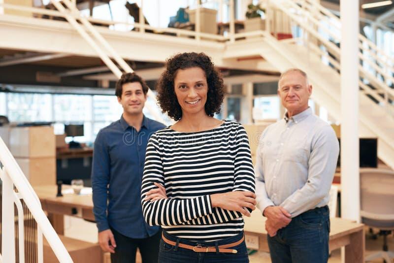 微笑的女实业家在有站立在她后的工友的一个办公室 库存照片