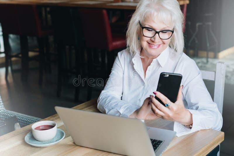 微笑的女实业家坐在膝上型计算机和使用智能手机前面的桌上 领抚恤金者自由职业者工作 免版税库存照片