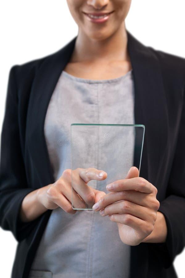 微笑的女实业家感人的玻璃接口的中间部分 免版税图库摄影