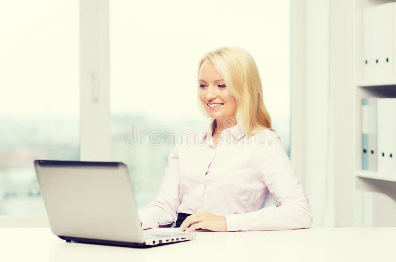 微笑的女实业家或学生有膝上型计算机的 库存图片