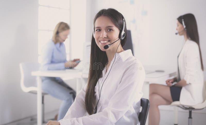 微笑的女实业家或热线服务电话操作员有耳机和计算机的在办公室 库存图片