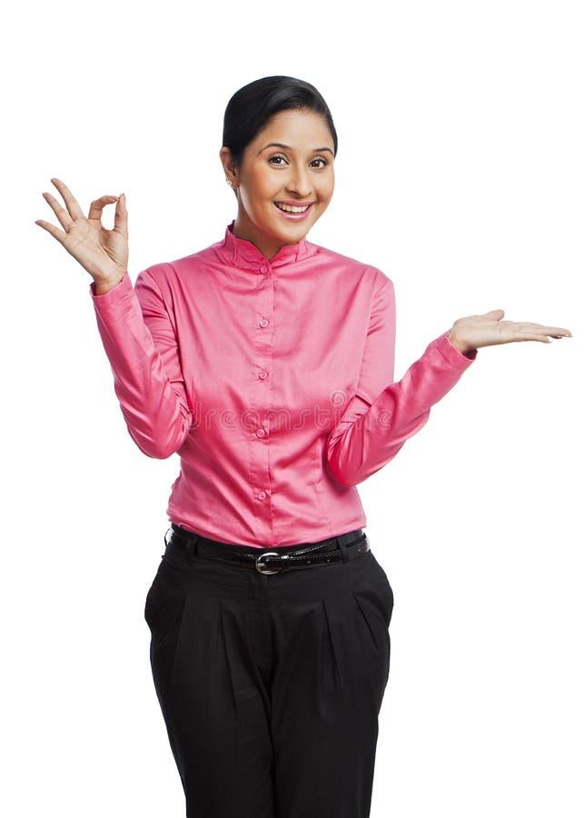 微笑的女实业家打手势和 免版税库存图片
