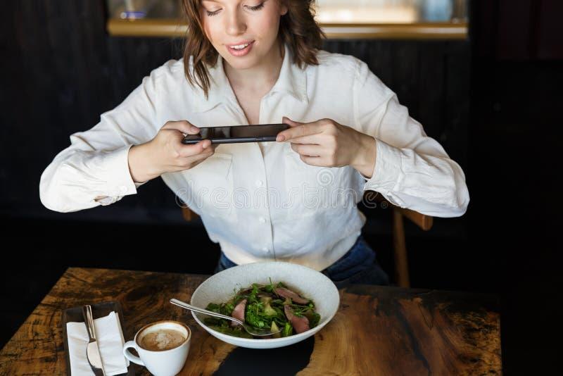微笑的女实业家有lucnch在咖啡馆户内 库存照片