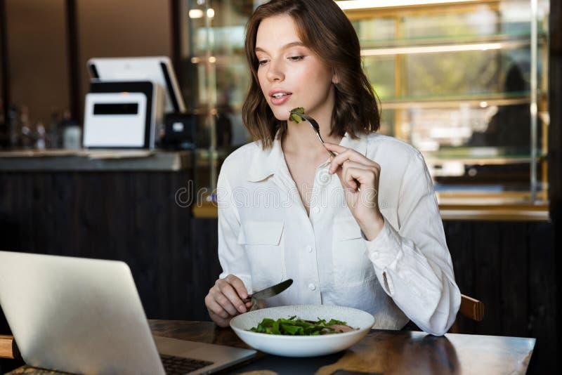 微笑的女实业家有lucnch在咖啡馆户内 免版税库存图片