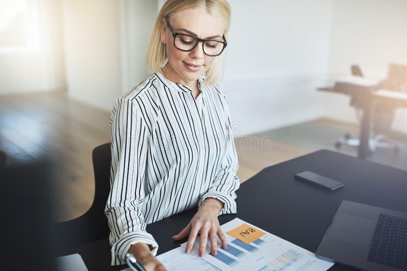 微笑的女实业家读书文书工作,当坐在她时 库存图片