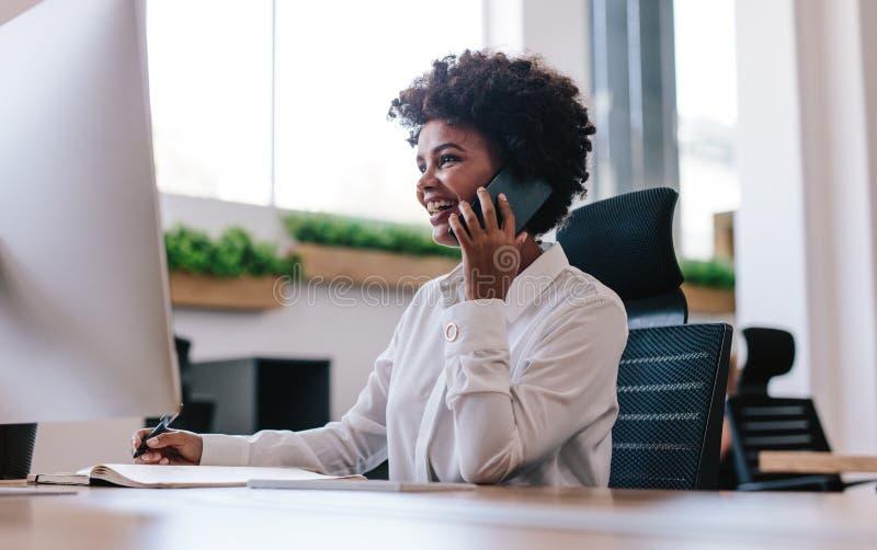 微笑的女实业家谈话与在电话的客户 免版税图库摄影