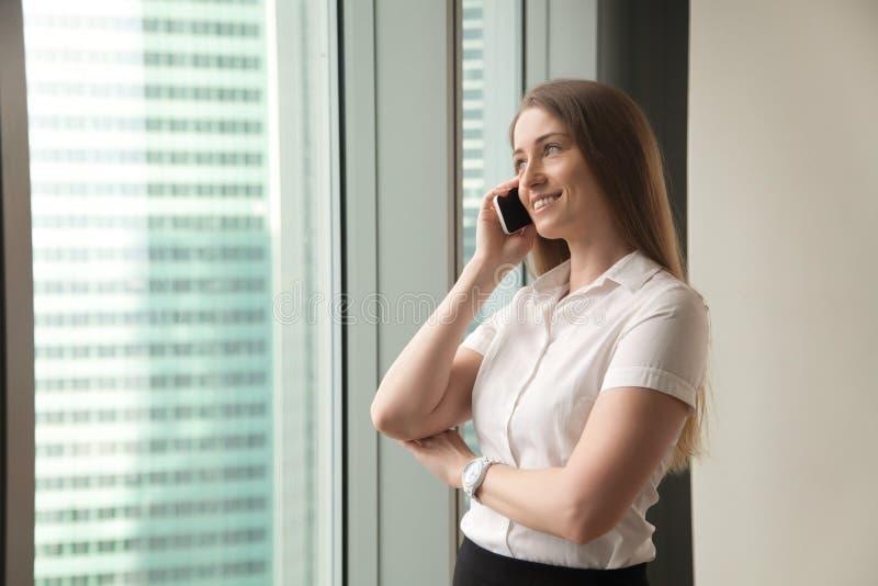 微笑的女实业家谈话在电话在办公室,做answeri 免版税库存图片