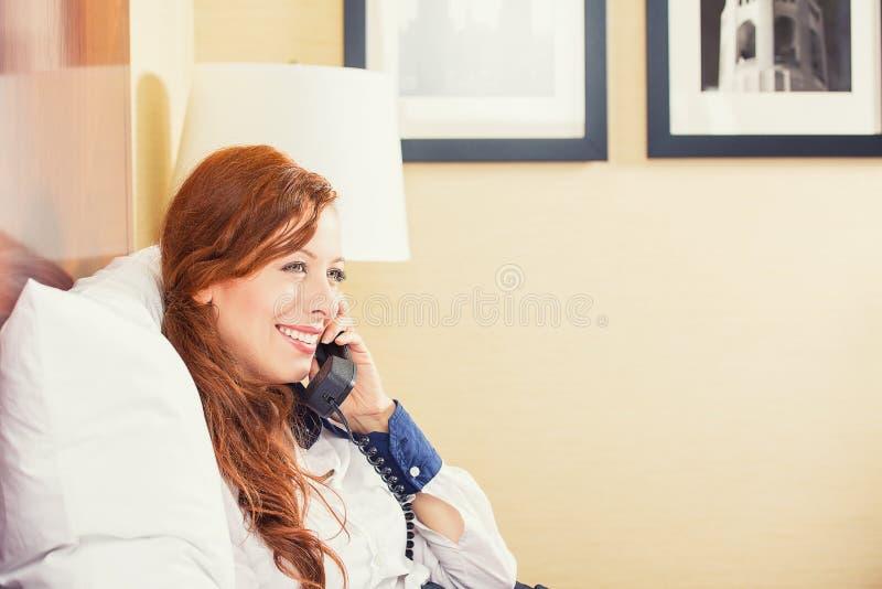 微笑的女实业家谈话在电话,当坐床在旅馆客房时 库存图片