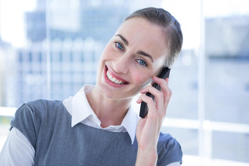 微笑的女实业家谈话在电话 库存图片